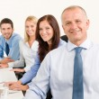 Business team happy sit in line behind table — Stock Photo #6935488