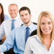Business team happy sit in line behind table — Stock Photo #6935493