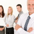 Businessman mature with colleagues stand in back — Stock Photo