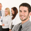 Businessman handsome with colleagues in the back — Stock Photo