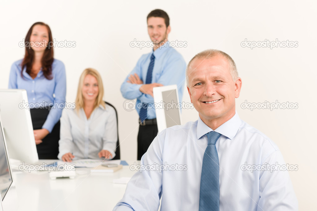 Business team happy mature businessman with attractive colleagues looking files  Stock Photo #6935453