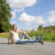Inline skates young woman sitting asphalt road — Stock Photo #7085645
