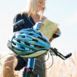 Mountain biking young woman search in map - 图库照片