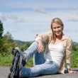 Inline skates young woman sitting asphalt road - Stock Photo