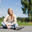Inline skates young woman sitting asphalt road — Stock Photo #7088211