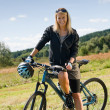 Mountain biking young woman sportive sunny meadows - Lizenzfreies Foto