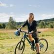 Mountain biking young woman sportive sunny meadows - Zdjęcie stockowe