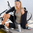 Sport biking young woman sitting by lake - Stock Photo
