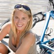 Sport biking young woman sitting by lake — Стоковая фотография