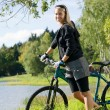 Mountain biking young woman relax by lake - Stock Photo