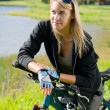Mountain biking young woman relax by lake — Stok fotoğraf