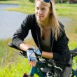 Mountain biking young woman relax by lake — Stock Photo