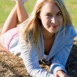 Sportive young woman relax on hay bales — Stock Photo #7088474