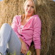Sportive young woman relax by bales sunset — Stock Photo #7088498