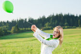Happy young woman with green balloon meadows — Stock Photo
