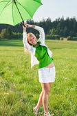 Happy young woman with green umbrella meadows — Stock Photo
