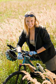 Mountain biking young woman sportive sunny meadows — Stok fotoğraf