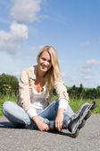 Inline brusle mladá žena sedící asfaltové silnici — Stock fotografie