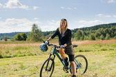 Mountain biking young woman sportive sunny meadows — Stock Photo