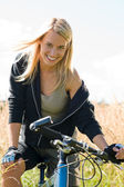 Mountain biking young woman sportive sunny meadows — Stock fotografie
