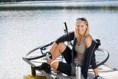 Esporte ciclismo jovem sentado ao lago — Fotografia Stock