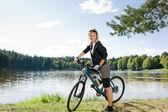 Mountain biking young woman relax by lake — Stock Photo
