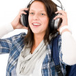 Smiling female teenager enjoy music headphones — Stock Photo