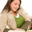 Student female teenager write homework with book — Stock Photo