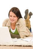 Student teenager girl typing laptop lying floor — Stock Photo