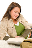 Student female teenager write homework with book — Stock Photo