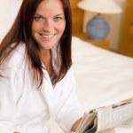 mujer atractiva Lee dormitorio de periódicos de la mañana — Foto de Stock