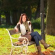 Autumn beautiful woman sit on bench park — Stock Photo