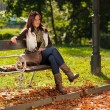 Autumn beautiful woman sit on bench park — Stock Photo #7357698