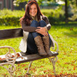 Autumn sunset park woman sitting on bench — Stock Photo
