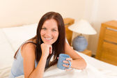 Bedroom - young woman drink coffee in bed — Stock Photo