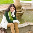 Autumn park young woman sit on fountain — Stock Photo