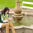 Autumn park fountain young woman read book — Stock Photo #7486055