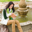 Autumn park fountain young woman read book — Stock Photo
