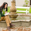Autumn park fountain young woman hold phone — Stock Photo #7486062