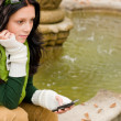 Autumn park fountain young woman hold phone — Stock Photo
