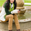 Autumn park bench young woman hold phone — Stock Photo #7486070