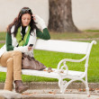 Autumn park bench young woman hold phone — Stock Photo