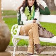 Autumn park bench young woman hold phone — Stock Photo #7486072
