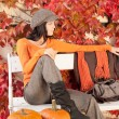 Autumn park bench young woman with pumpkins — Stock Photo