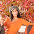 Autumn park bench young woman relaxing — Stock Photo
