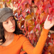 Autumn park bench young woman touch leaf — Stock Photo