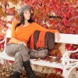 Autumn park bench young woman relaxing - Stock Photo