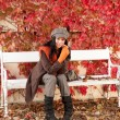 Autumn park bench young woman relaxing — Stock Photo #7486105