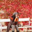 Autumn park bench young woman relaxing — Lizenzfreies Foto