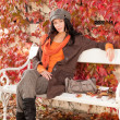 Autumn fashion portrait young woman relax bench - Stock Photo